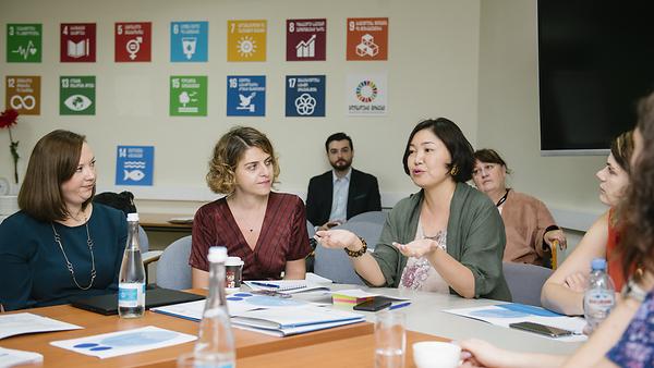 Mehrere Diskussionsteilnehmer auf am Tisch bei einem Workshop zu den Nachhaltigen Entwicklungszielen