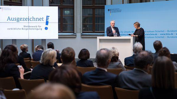 Foto von einer Veranstaltung des Wettbewerbs für vorbildliche Bürgerbeteiligung im Jahr 2018, auf der Bühne stehend